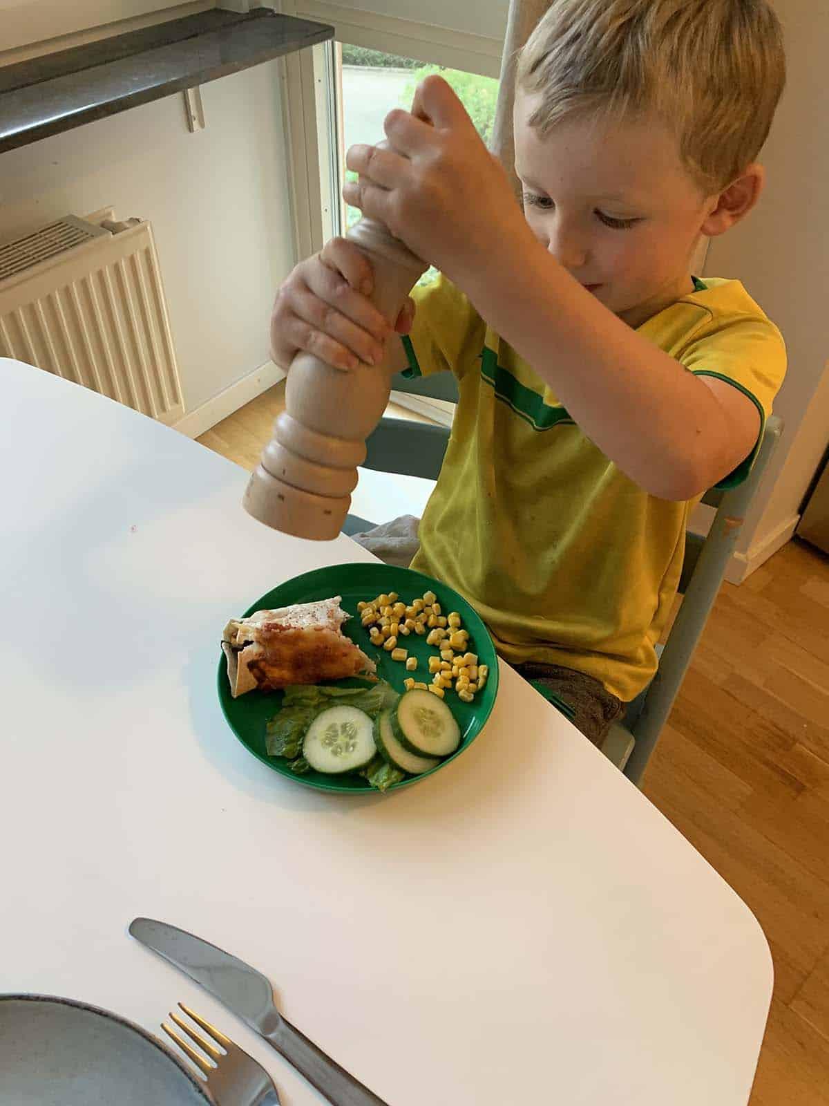 A boy in a yellow shirt holding a wooden pepper grinder