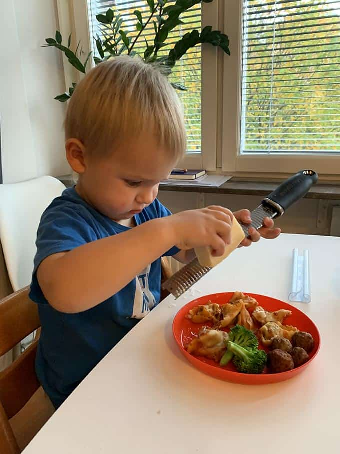 a blond boy in a blue shirt grating parmesan over a plate of pasta