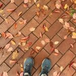 a woman's feet in blue sneakers on a brick road covered in leaves