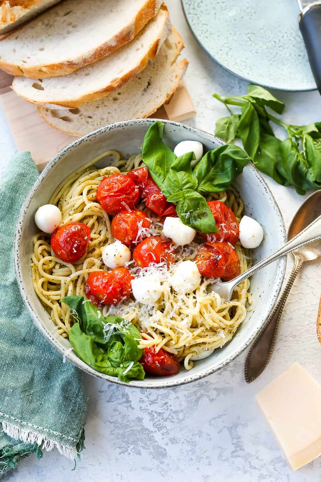overhead photo of vegetarian pesto pasta topped with roasted tomatoes and mozzarella in a blue bowl