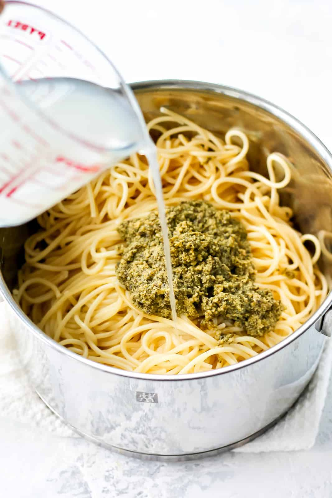 pasta water being poured into a pot of spaghetti and pesto