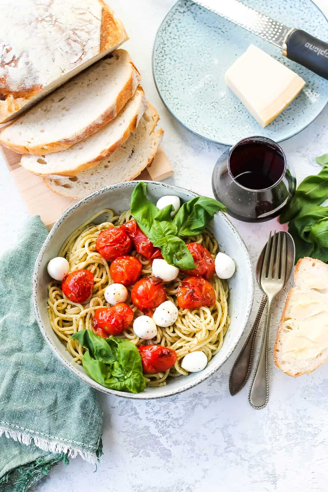 overhead photo of spaghetti al pesto in a blue bowl topped with tomatoes and mozzarella