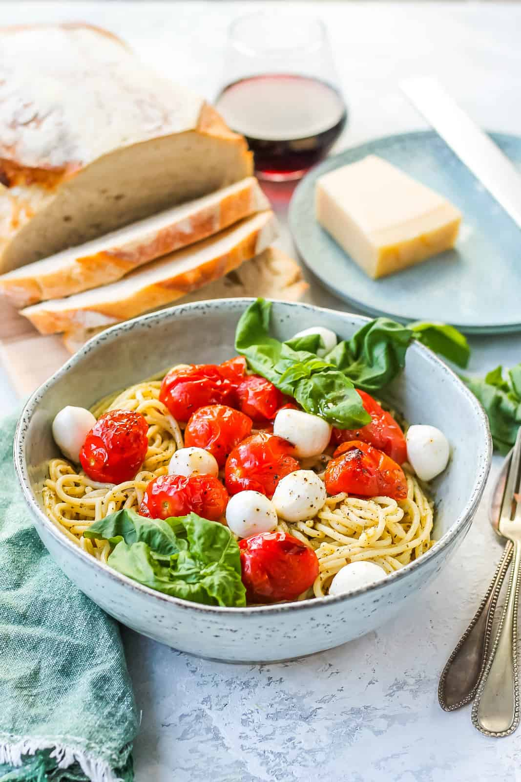 a bowl of vegetarian pesto pasta with tomatoes and mozzarella with a loaf of bread and a glass of wine in the background