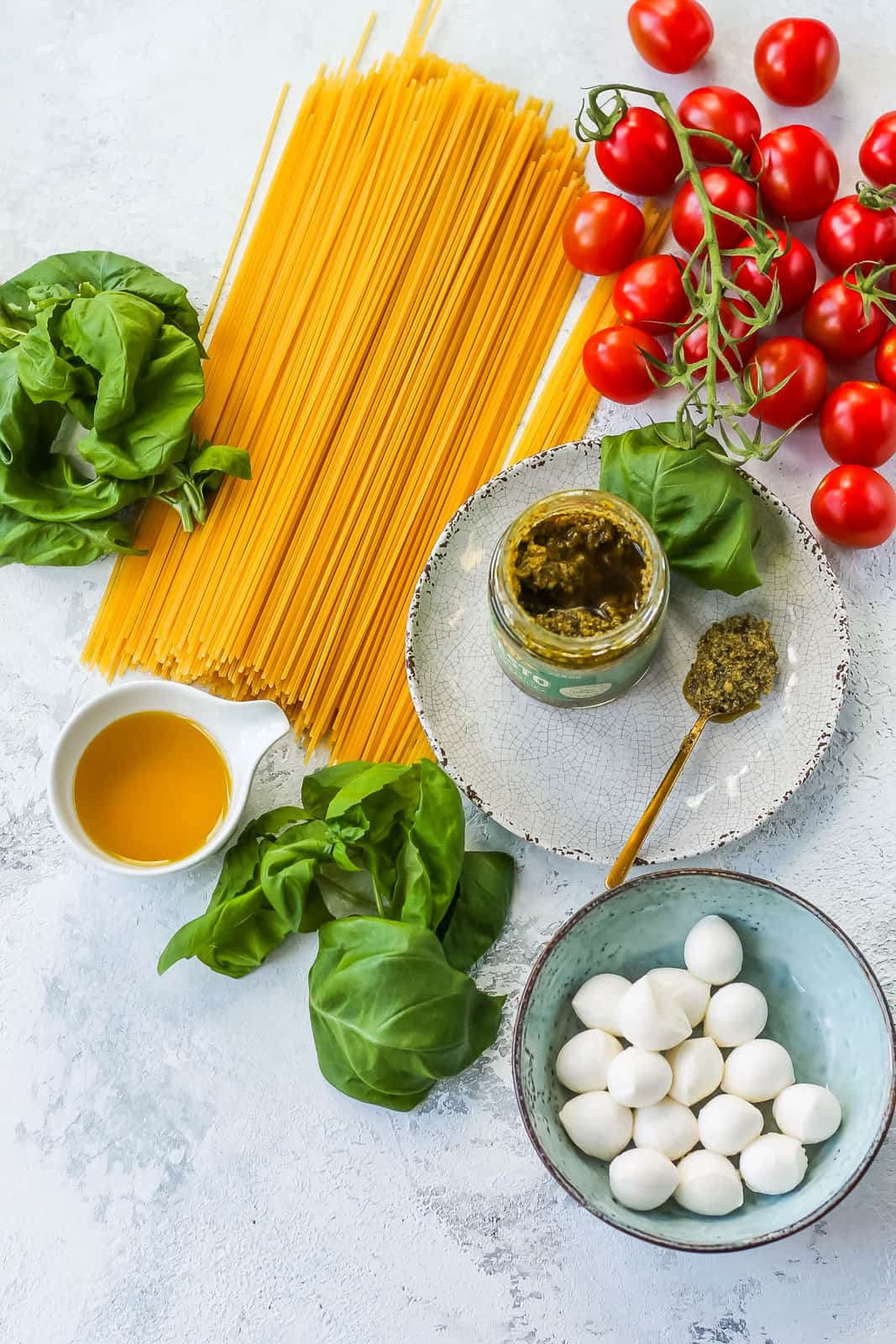 spaghetti, basil, olive oil, jarred pesto, cherry tomatoes, and mozzarella balls on a grey background