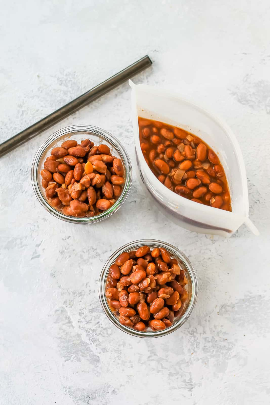 overhead photo of pinto beans in glass jars for freezing