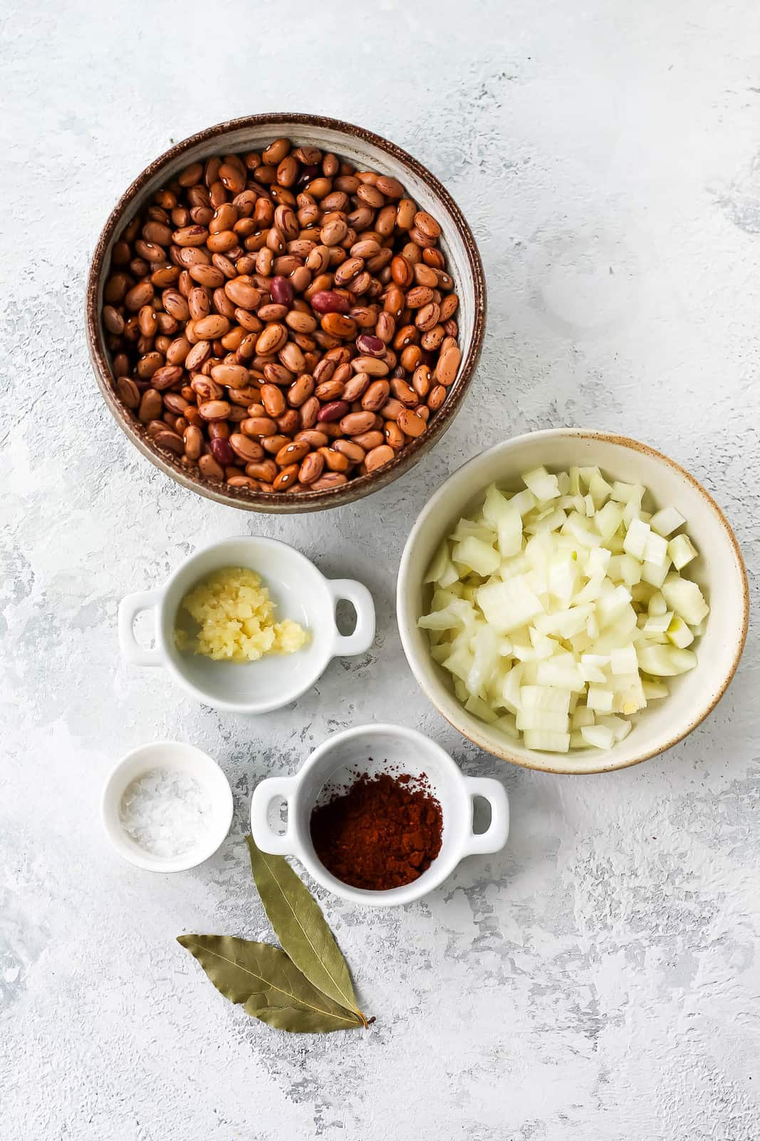 pinto beans, diced onion, garlic, chili, bay leaves, and salt on a grey background