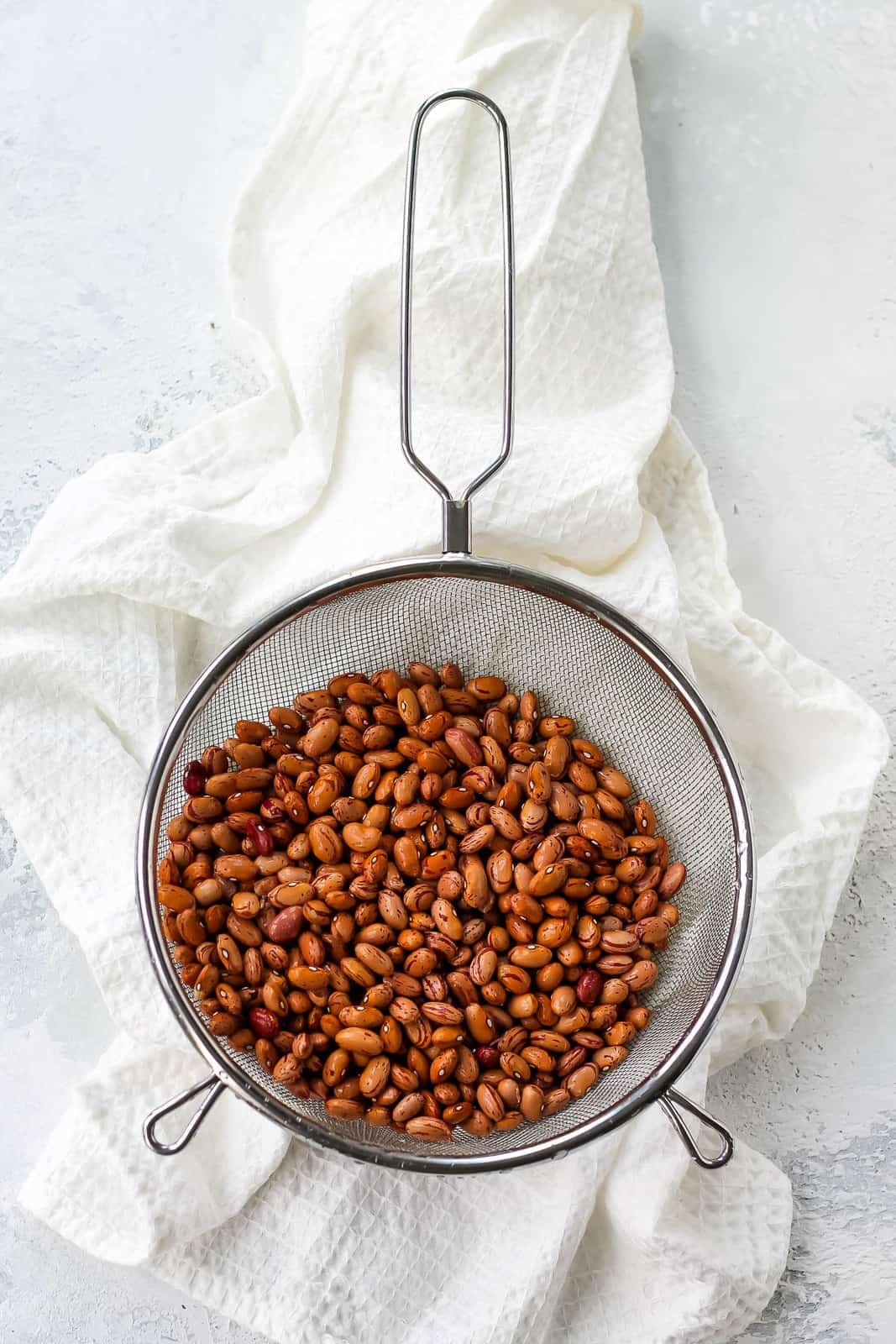 overhead photo of pinto beans in a mesh strainer