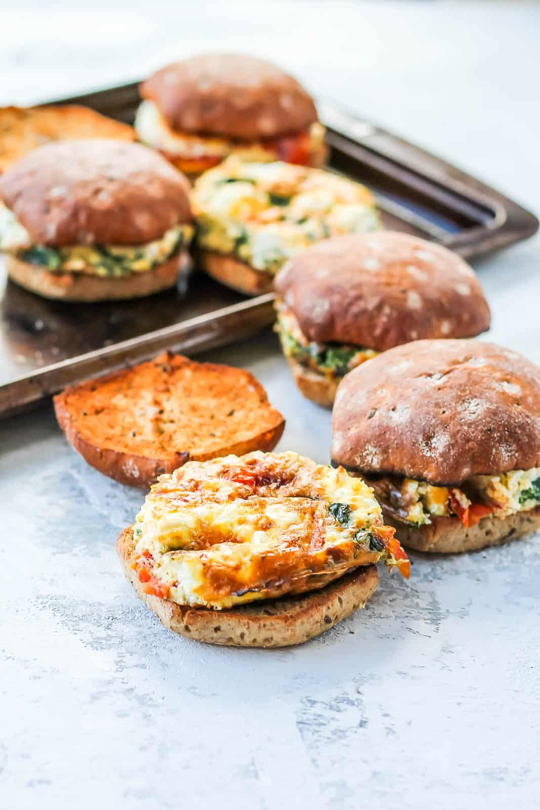 a tray with vegetarian breakfast sandwiches on a grey background