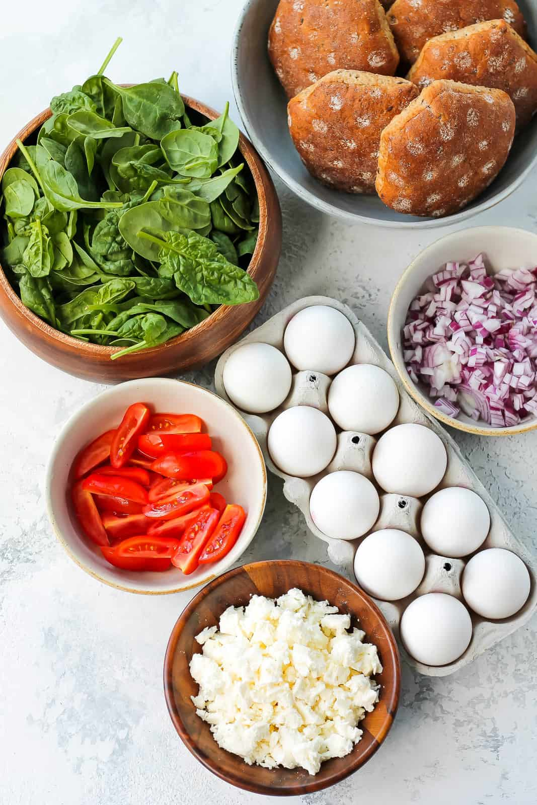 eggs, feta, spinach, tomatoes, red onion, and whole grain buns on a grey background