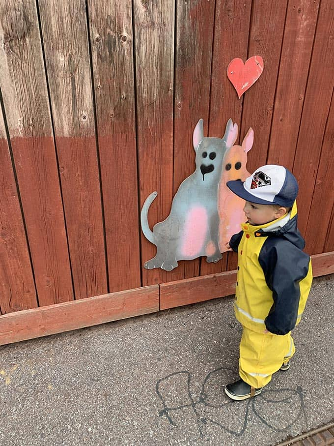 a boy in yellow rain pants beside a drawing of two dogs on a wall