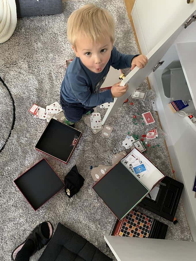 a small boy standing in between a mess of board game boxes on the floor
