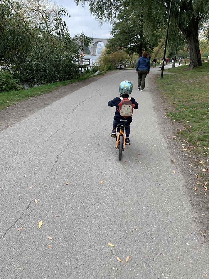 a boy riding an orange bike on a path by the water