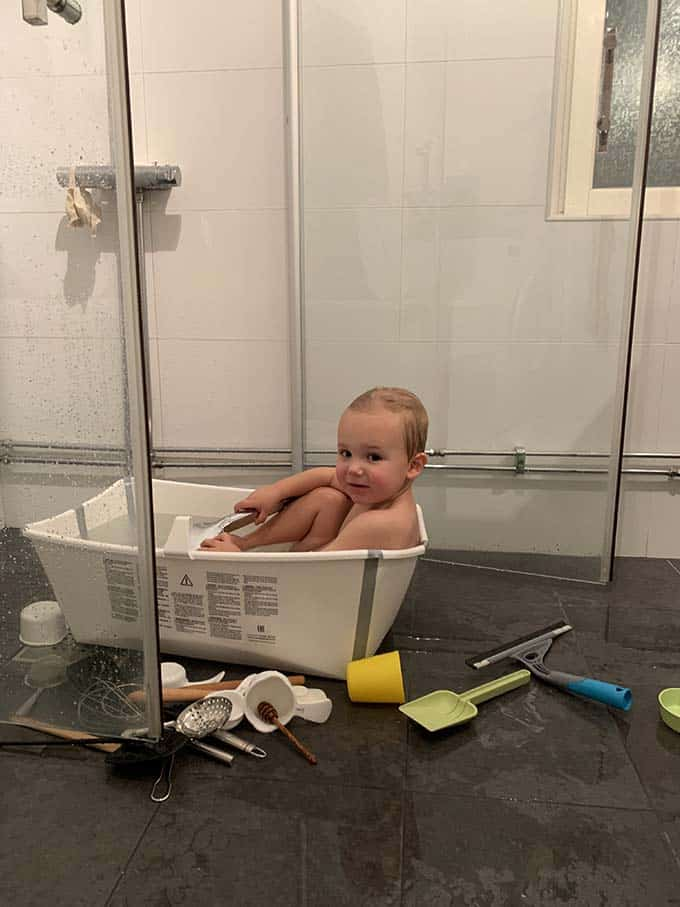 a small boy in a little bath tub with kitchen tools strewn on the floor