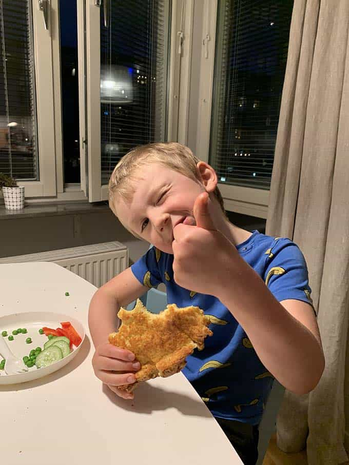 a boy eating a slice of pancake giving a thumbs up