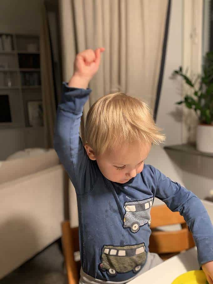 a boy in a blue shirt with one arm up in the air