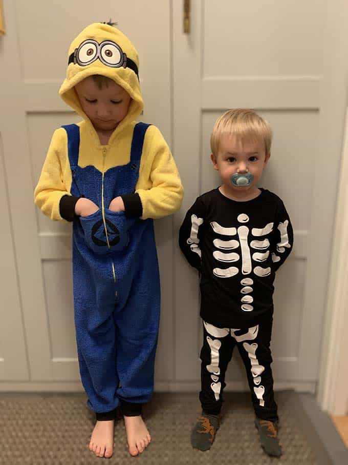 A boy in a minion costume and a small boy with a pacifier wearing a skeleton costume