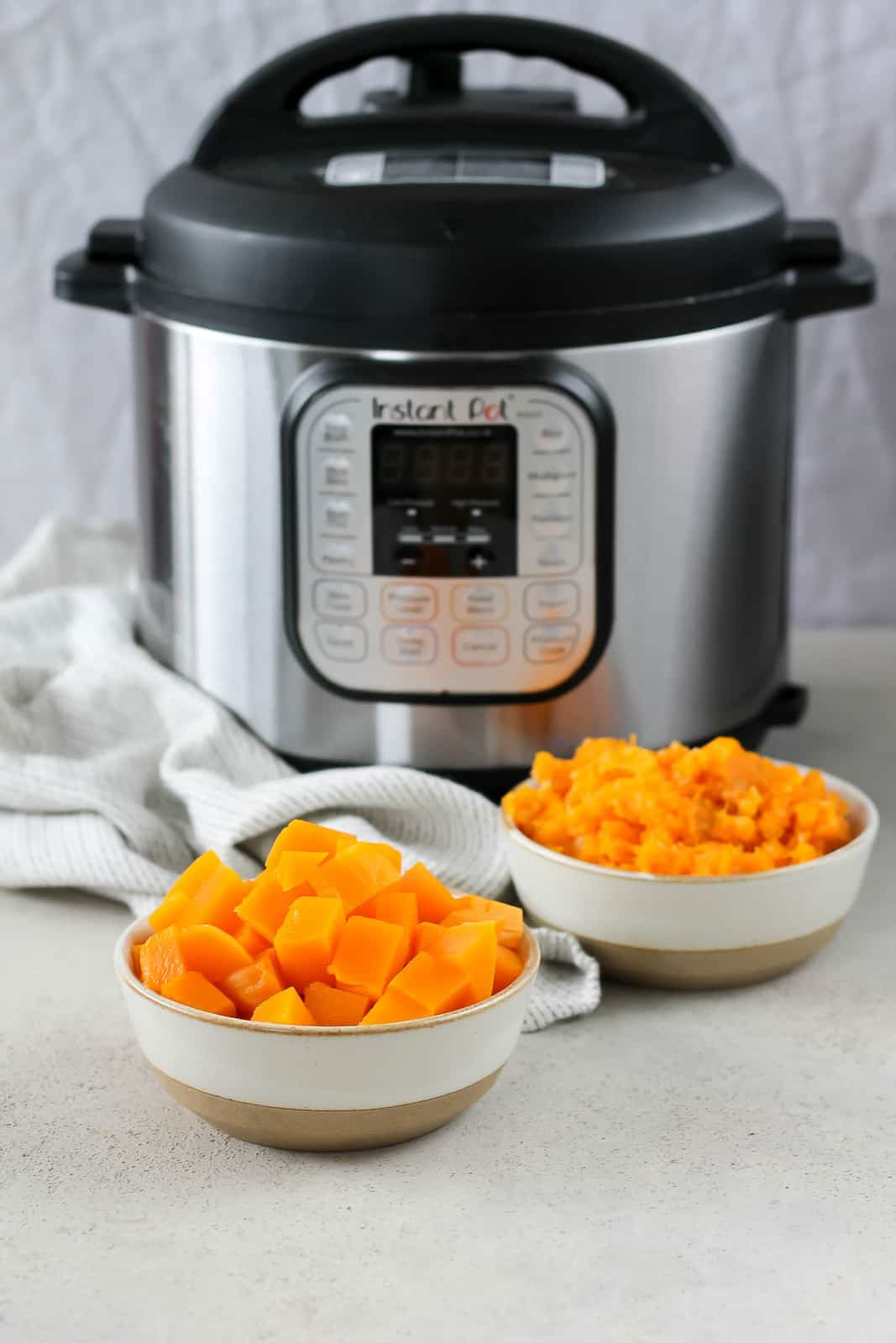 a bowl of cubed butternut squash and a bowl of mashed squash in front of an instant pot