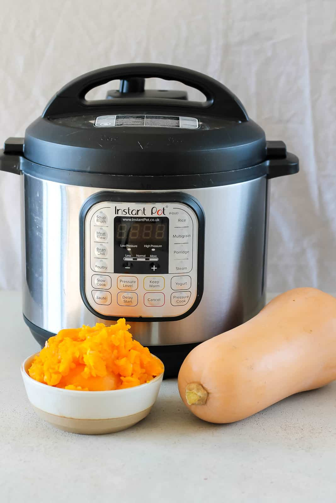 a bowl of mashed butternut squash and a whole butternut squash in front of an instant pot
