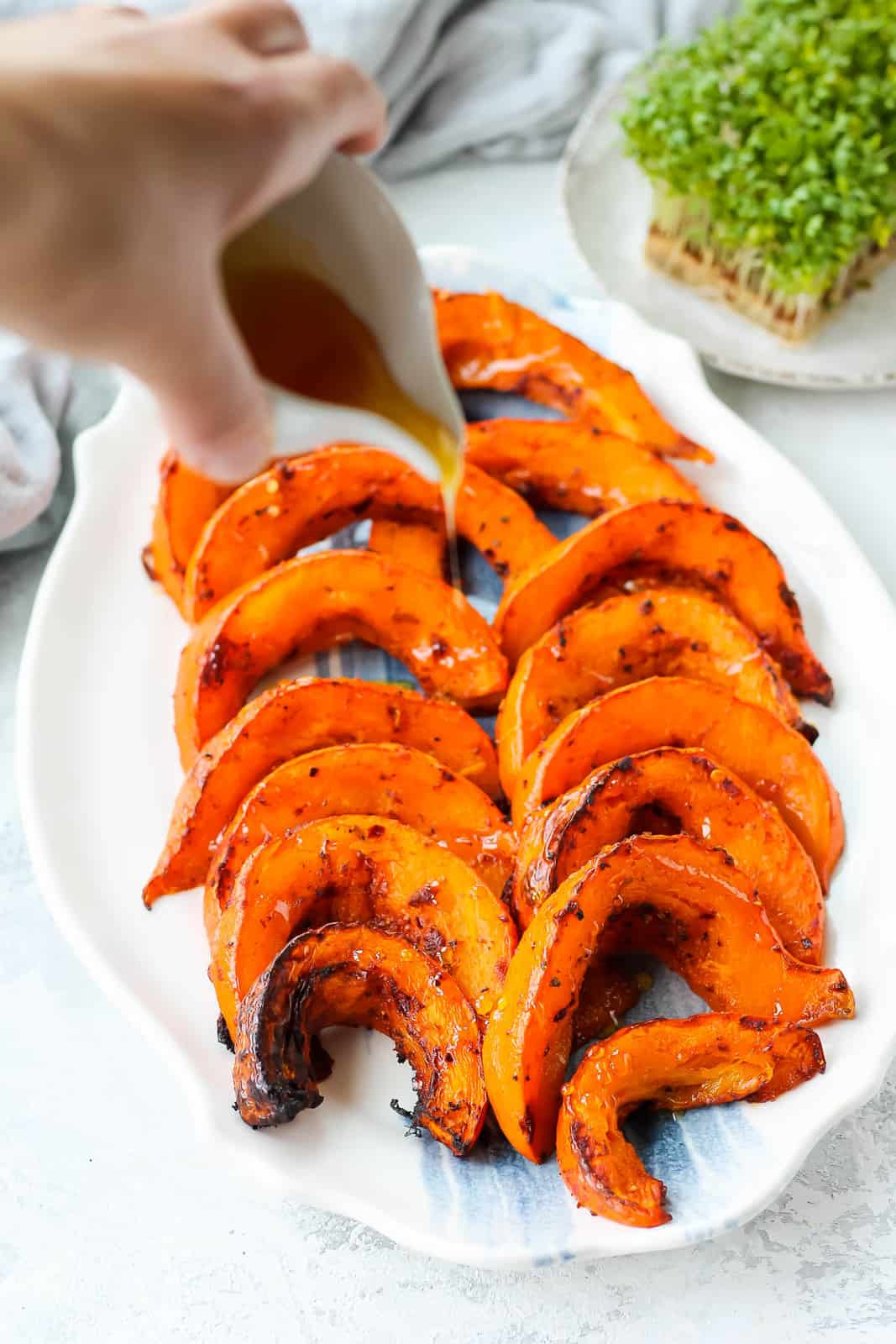 honey being drizzled onto roasted pumpkin slices on a white and blue platter