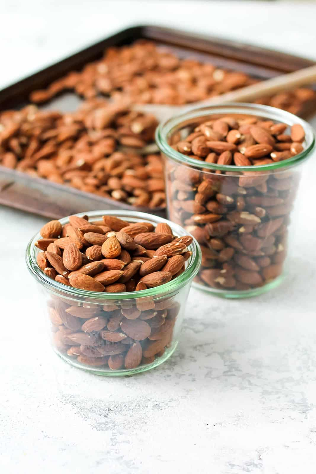 two glass jars of oven roasted almonds with a tray of toasted almonds in the background