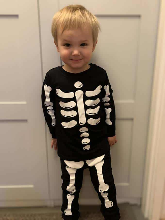 a small boy in a skeleton costume