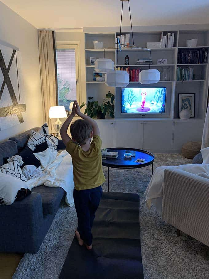 a young boy doing yoga in front of the tv