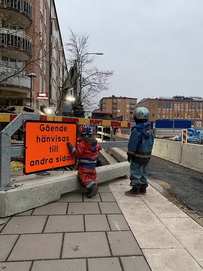 two boys watching an excavator work