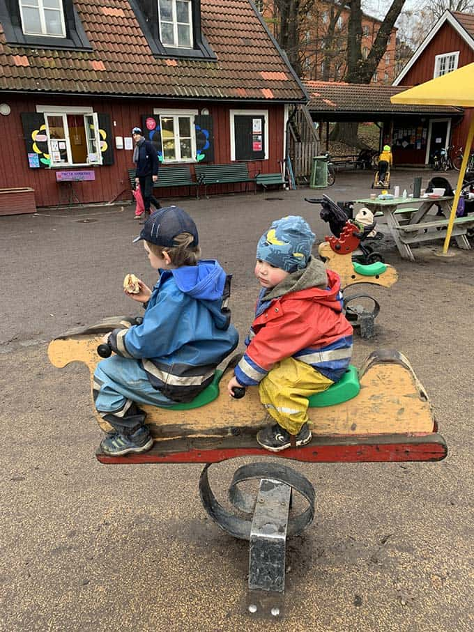 two boys in rain gear on a rocking horse in a playground