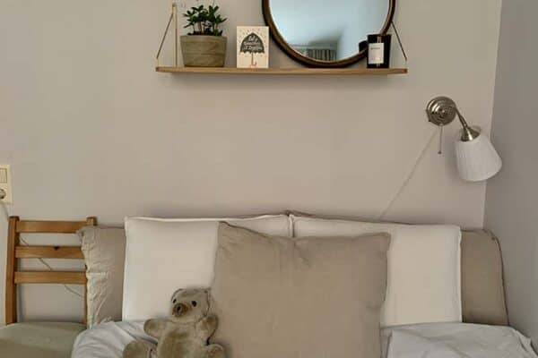 a bed with beige and white sheets on it, with a shelf and mirror above the bed.