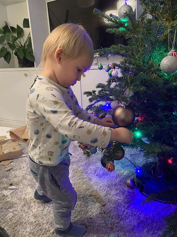 a small boy hanging ornaments on a tree