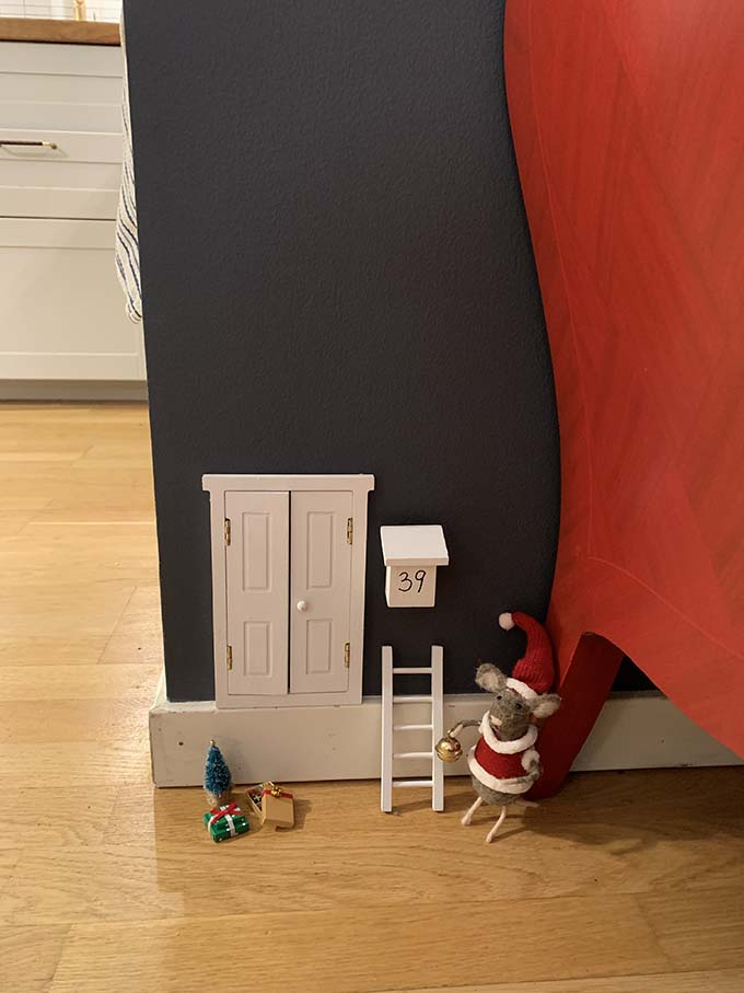 A tiny door, mailbox, ladder, and christmas tree fastened to a blue wall