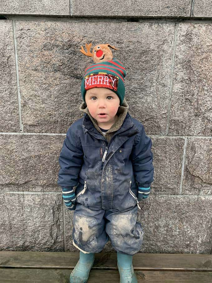 """a small boy in a muddy blue overall wearing a hat that says """"merry"""" with a reindeer on the top"""