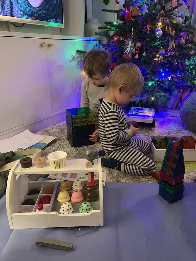 two small boys opening presents beside a christmas tree