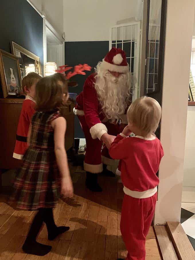three kids meeting santa in an apartment