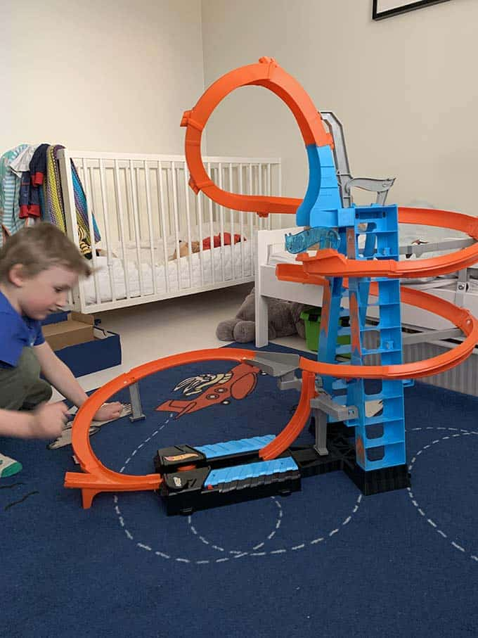 a boy with a hotwheels race track set up in his bedroom