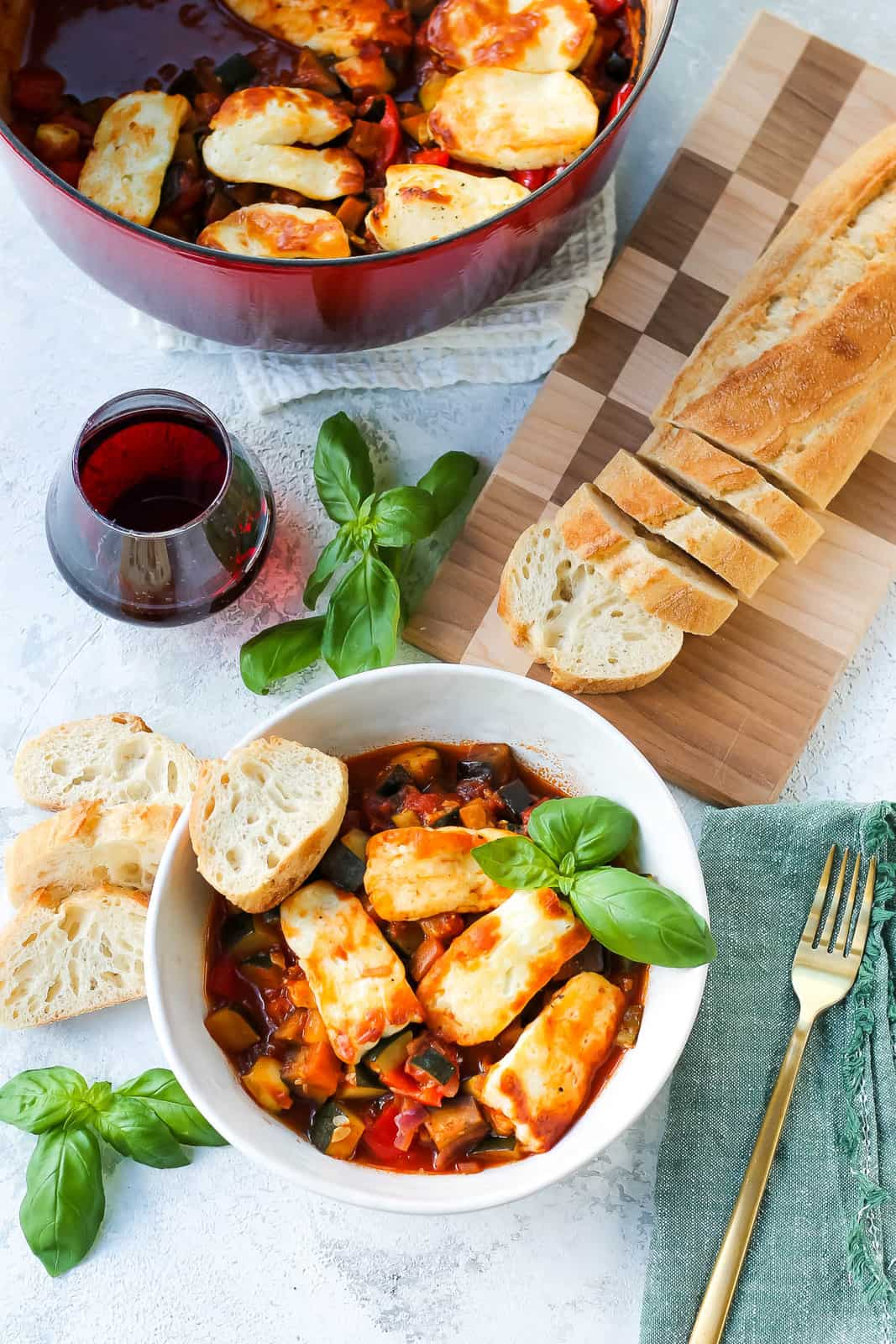 overhead photo of baked halloumi with vegetable ratatouille in a white bowl with a sliced baguette and a glass of red wine on a grey surface