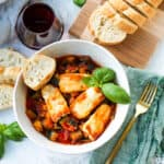 overhead photo of baked halloumi with vegetable ratatouille in a white bowl with a gold fork and a green napkin to the side