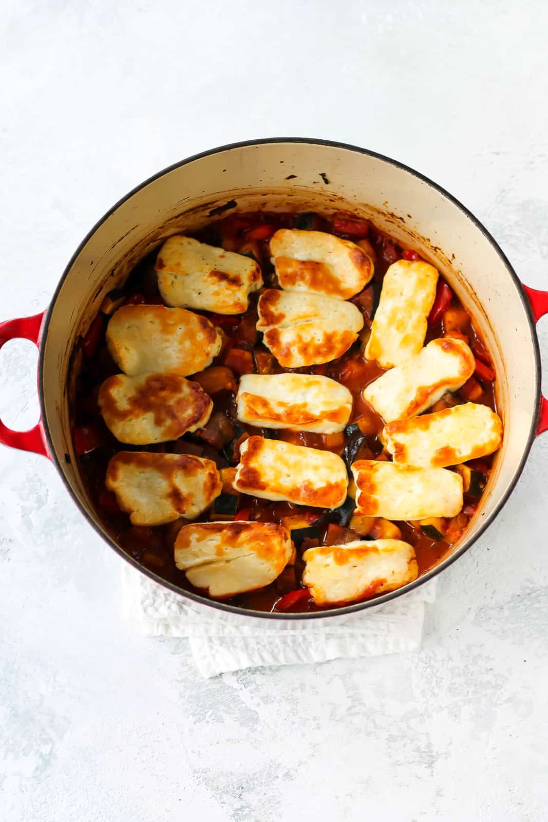 overhead photo of baked halloumi in a red dutch oven
