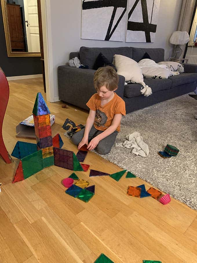 a boy in an orange t-shirt playing with magnetic blocks