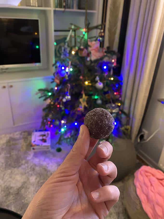a hand holding a chocolate rum ball in front of a christmas tree