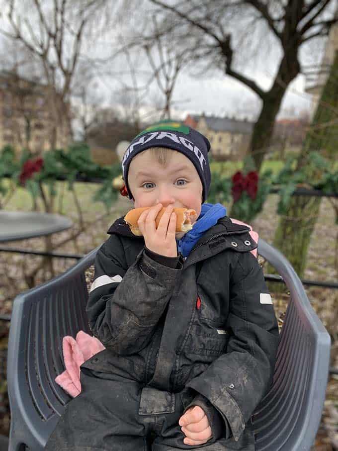 A boy eating a hotdog outside