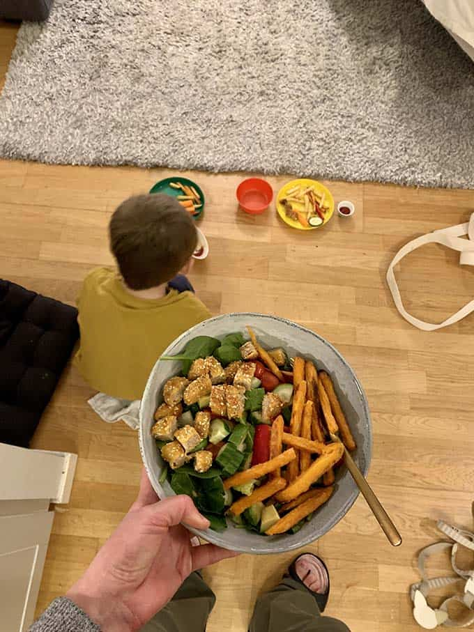 a woman's hand holding a bowl of salad and french fries over a boy eating from a plate on the floor