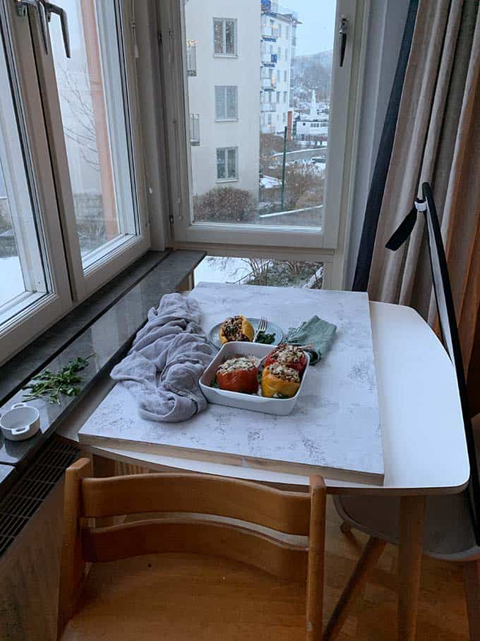 a tray of stuffed peppers on top of a photo backdrop with a reflector set up beside a table by a window