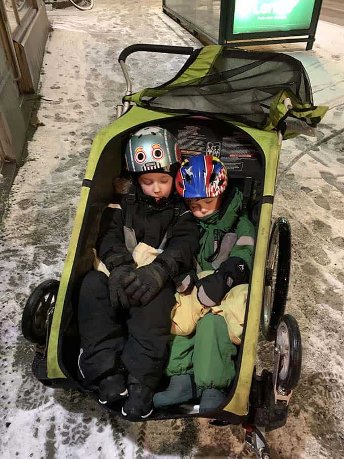 two sleeping kids in a green Thule double wagon