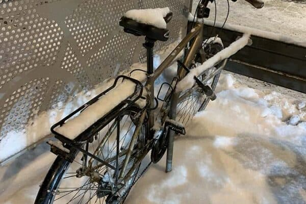 a parked bike covered in snow