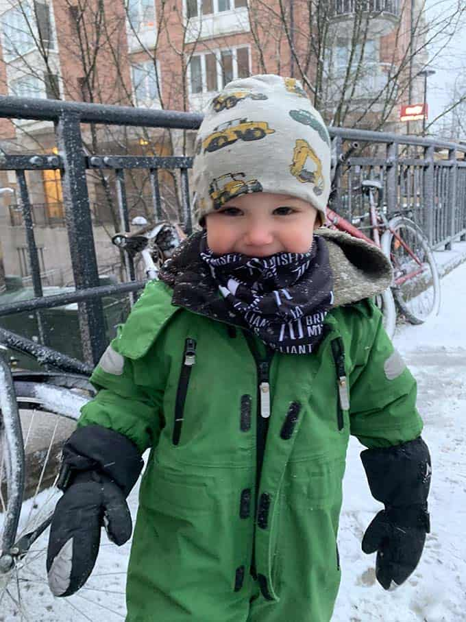 a small boy in a green snowsuit
