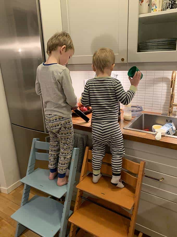 two boys standing on stokke stools in a kitchen