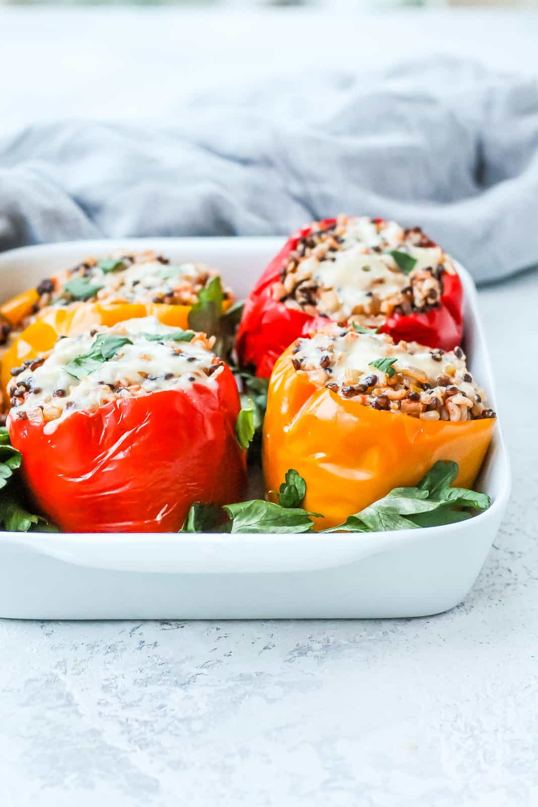 red and yellow vegetarian stuffed peppers topped with cheese in a white casserole dish