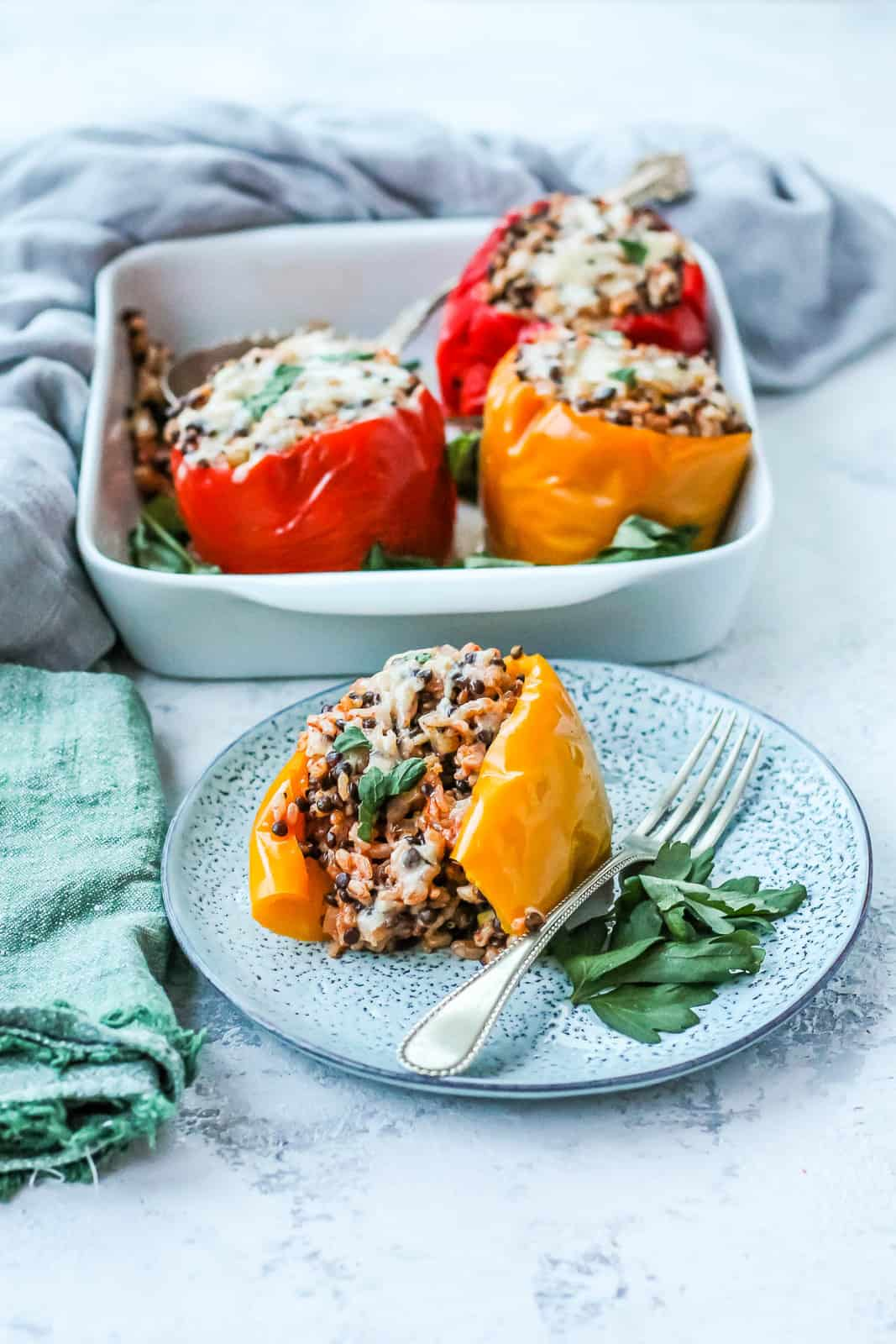 a yellow vegetarian stuffed pepper on a white plate with a silver fork on the side, and a casserole dish with three more stuffed peppers in the background