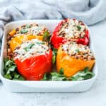 four vegetarian stuffed peppers in a white casserole dish